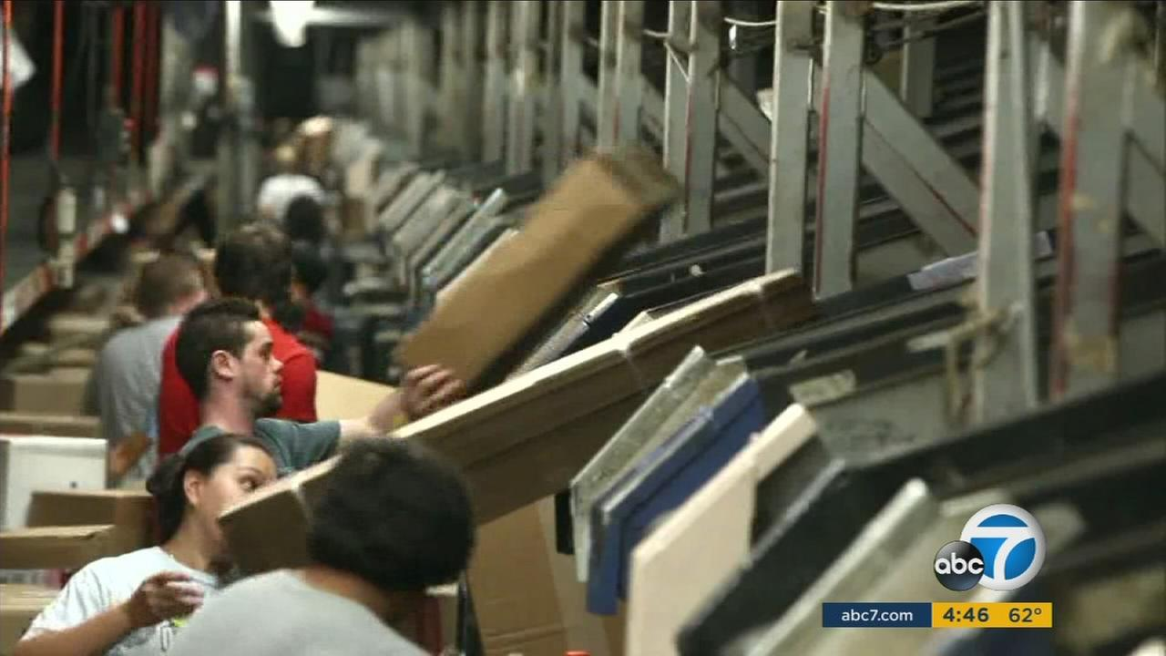 Workers package items that are expected to ship during the holiday season.