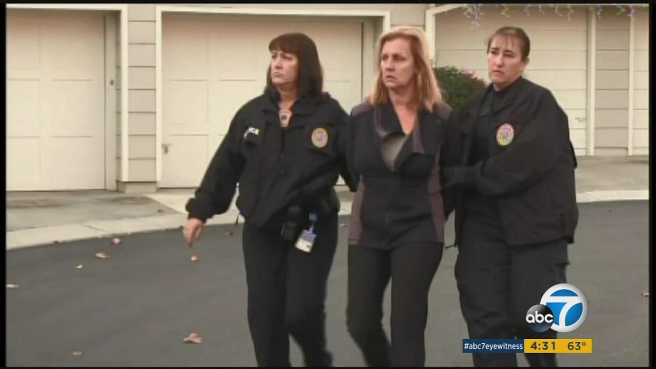 Kristi McKinlay, 56, is taken into custody in an undated photo.