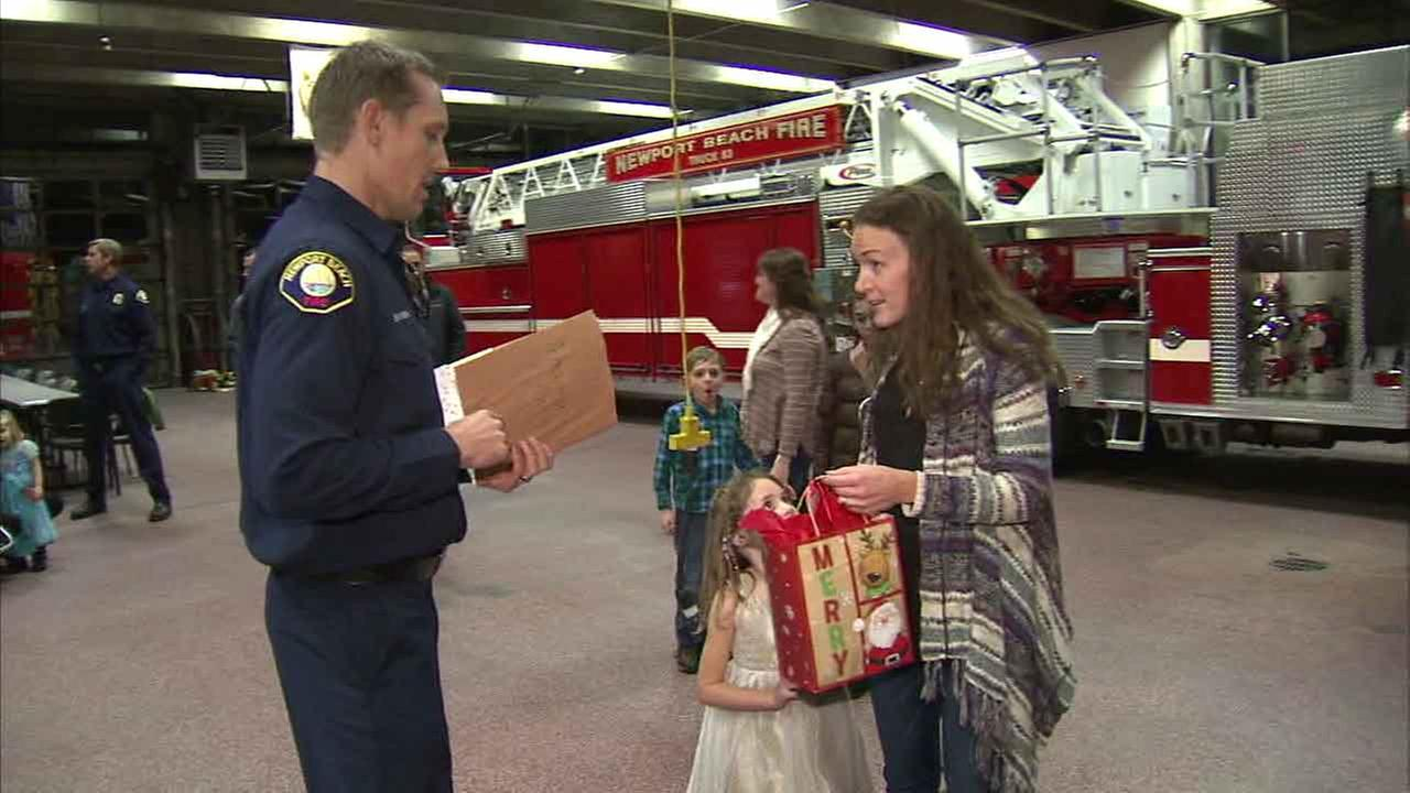 A Newport Beach firefighters gives Renee Wetzel one of many surprises for her family on Sunday, Jan. 3, 2016.