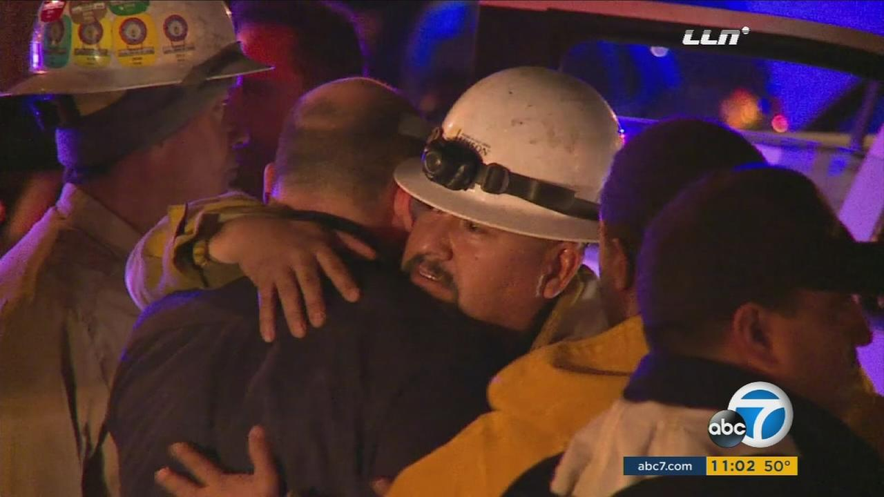 Workers with Southern California Edison comfort each other after one of their co-workers was electrocuted in Paramount on Wednesday, Jan. 6, 2016.