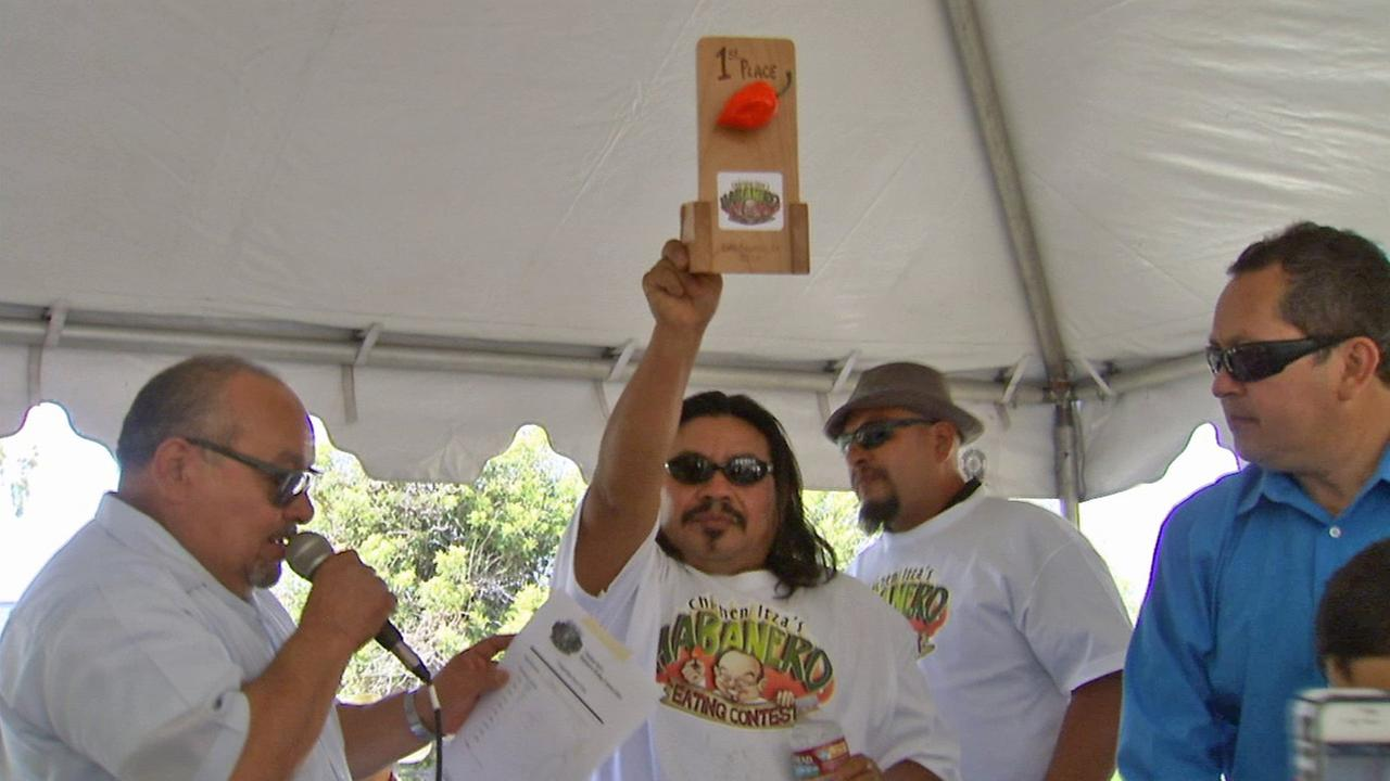 A man holds up his first place plaque after winning a habanero eating contest in downtown L.A. on Sunday, June 15, 2014.