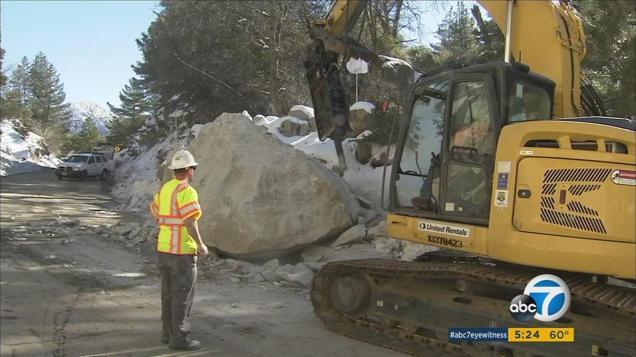 Caltrans crews work to remove a large boulder from Highway 243 near Idyllwild in Riverside County on Tuesday, Jan. 12, 2016.