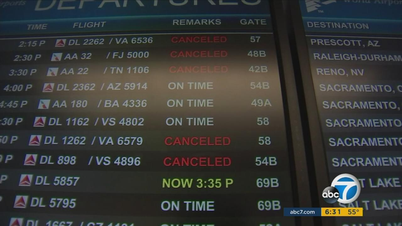 A display sign shows canceled or delayed flights out of LAX headed to the East Coast on Saturday, Jan. 23, 2016.