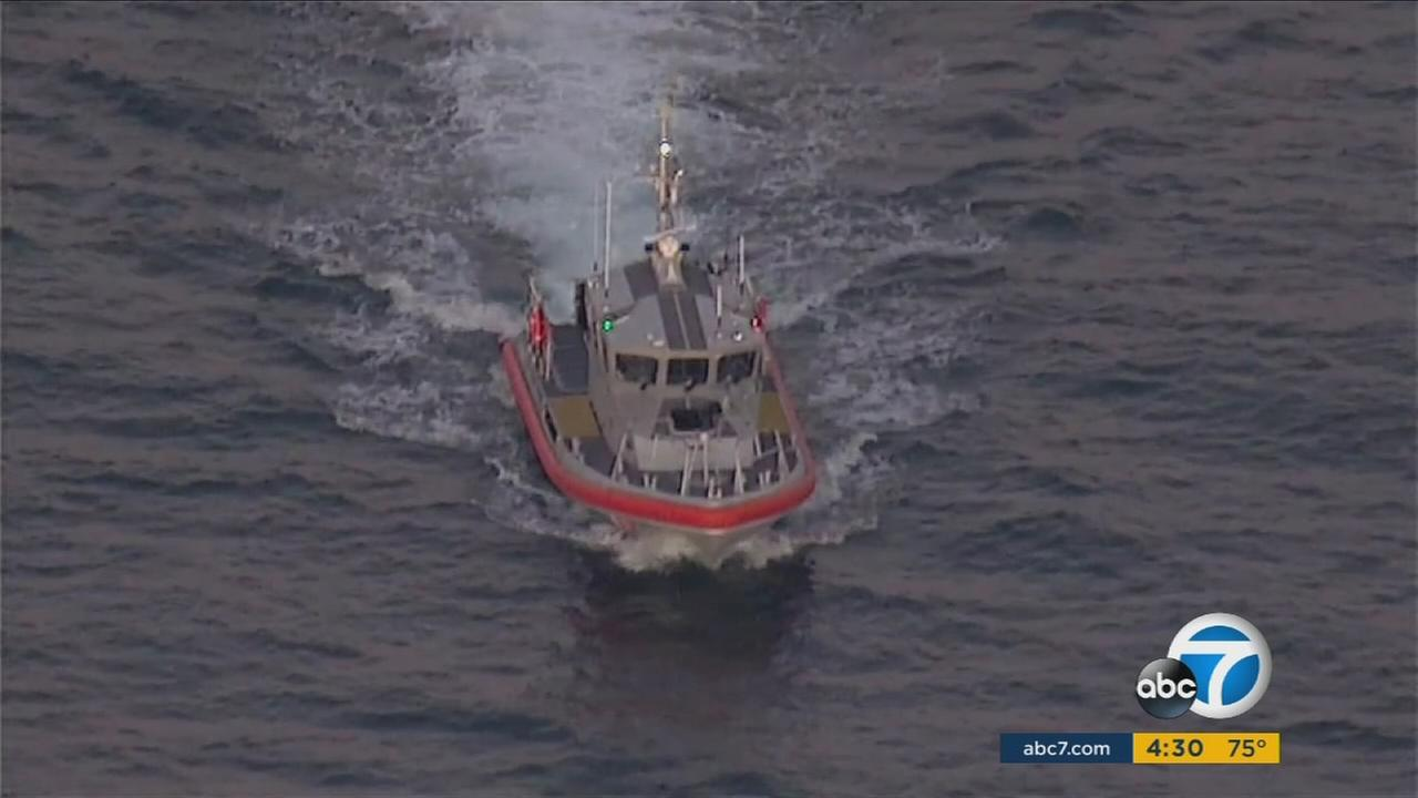 A U.S. Coast Guard boat conducts a recovery effort after two planes are suspected of crashing midair near San Pedro.