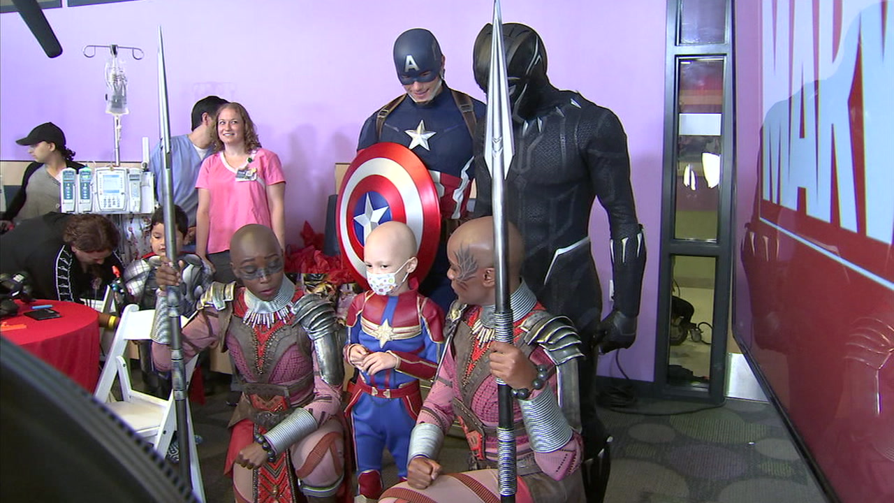 A child in a Captain Marvel suit is shown as she takes a photo with other Marvel superheroes at Childrens Hospital Los Angeles.