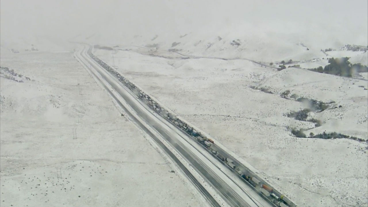 Cars are shown stalled for miles on the 5 Freeway in the Grapevine as snow falls and blocks roads.