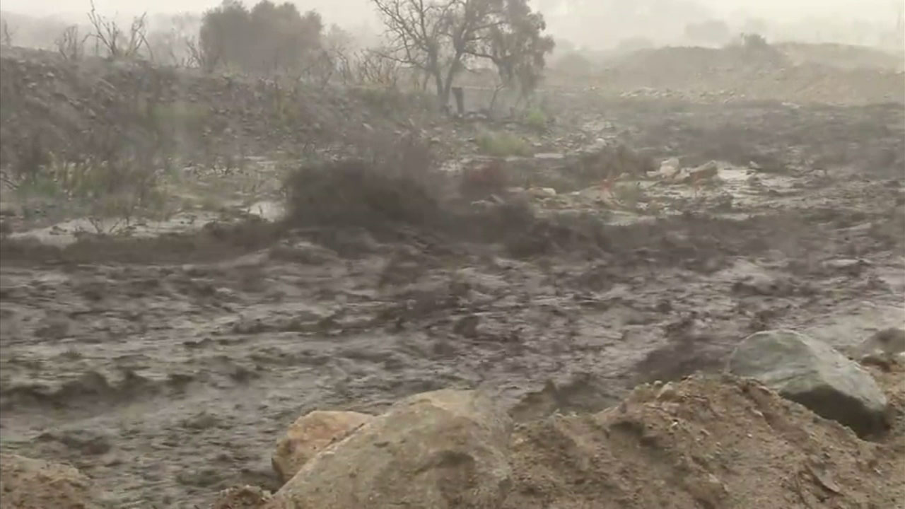 Mud flows through Rice Canyon as heavy rains inundate Lake Elsinore.