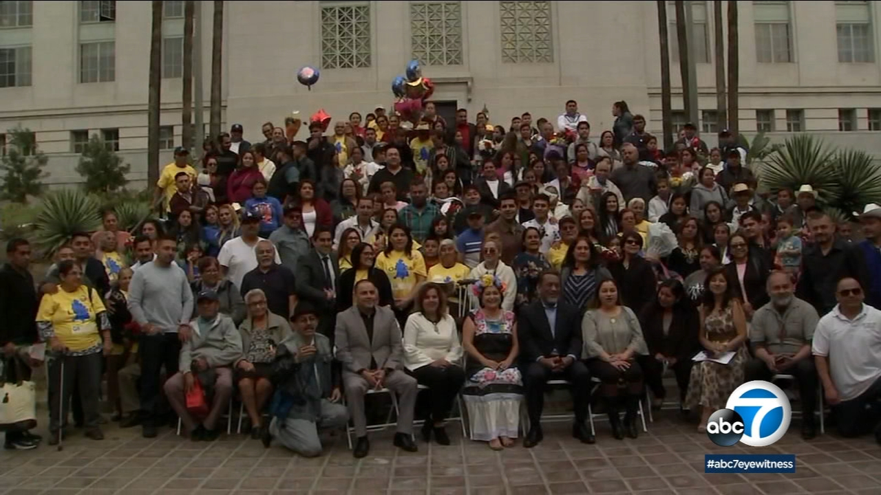 Immigrant families who were reunited for the holidays are shown in a photo at City Hall in downtown L.A.
