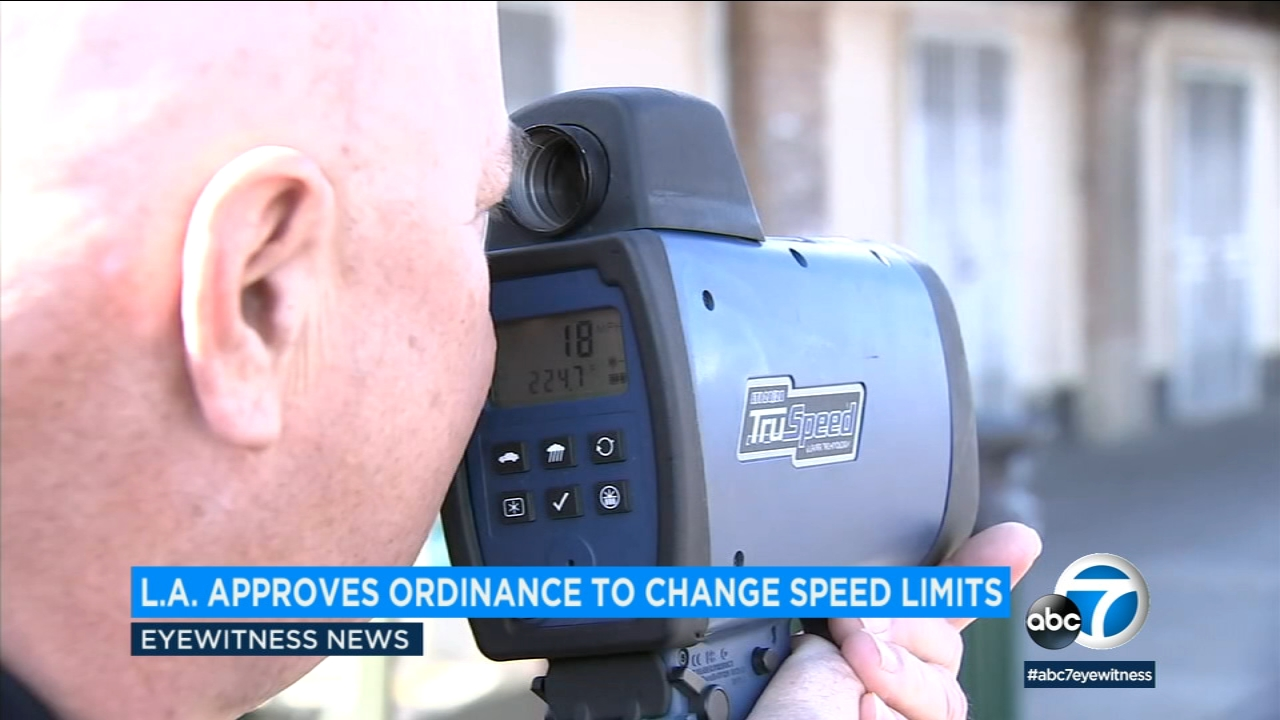 A law enforcement officer uses a radar device to detect the speed of passing vehicles.