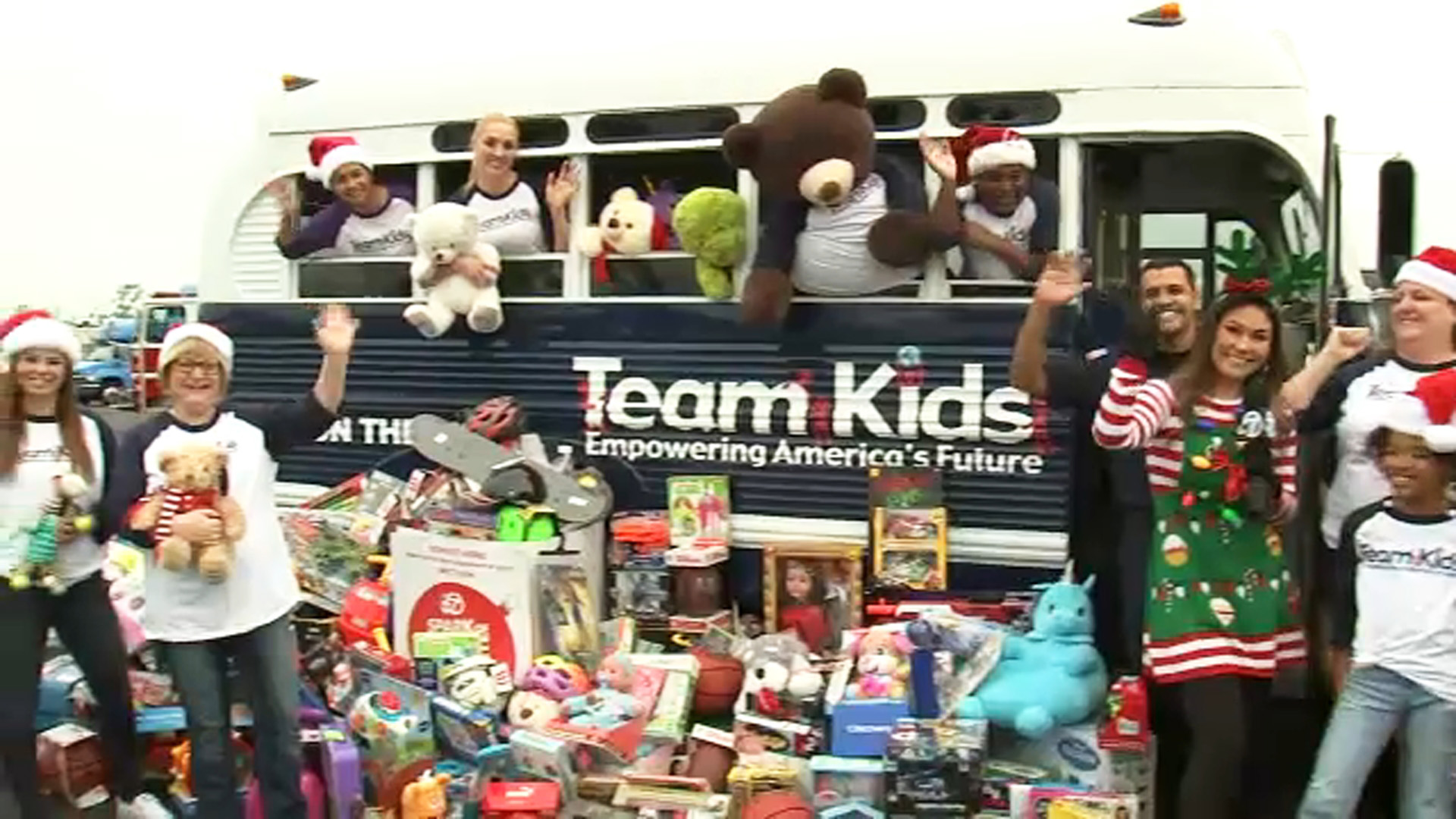 Spark of Love participants wave with ABC7s Kimi Evans as more trucks are filled for the annual toy drive on Friday, Dec. 14, 2018.