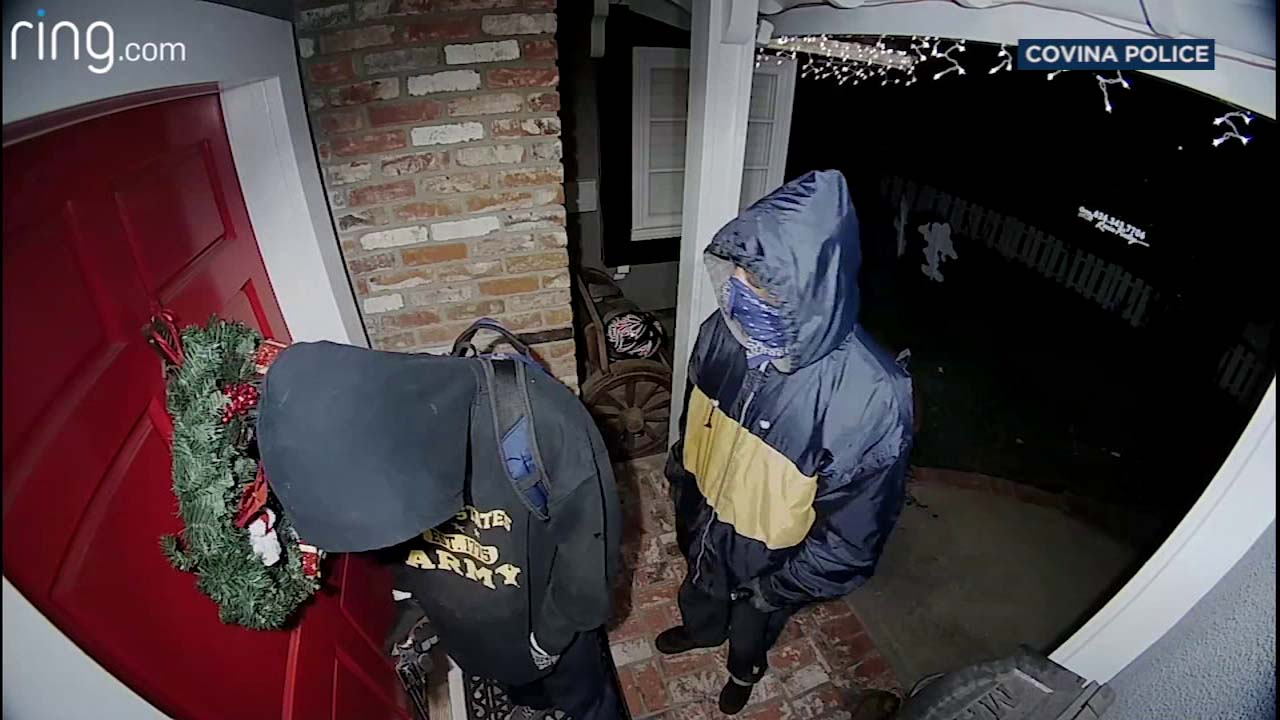Two men are seen at the front door of a home in Covina on Tuesday, Dec. 18, 2018.