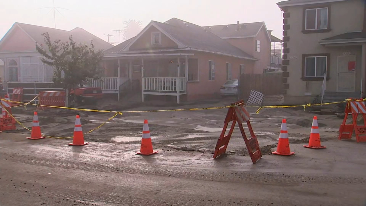 The area where a pipe burst and created a sinkhole is shown in front of homes in South Los Angeles.