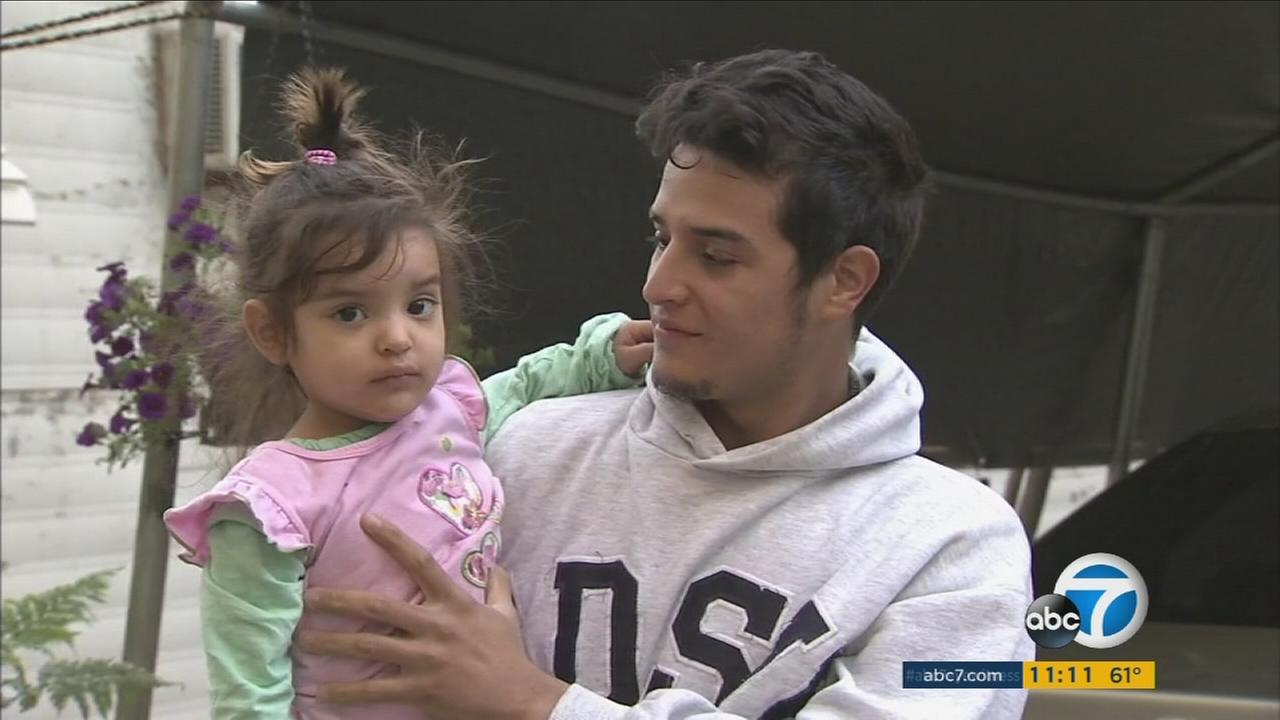Nilson Jimenez holds his daughter Yesly, 2, after she survived a kidnapping in their mobile home park, northeast of Santa Clarita.