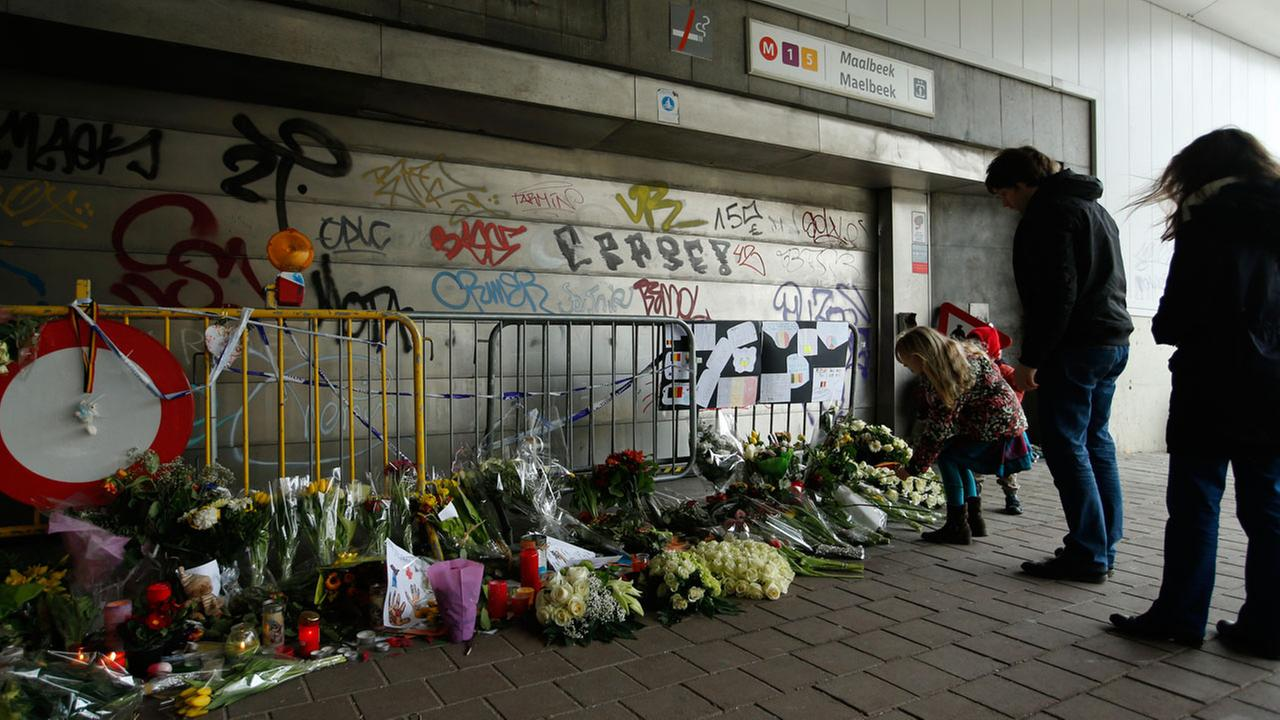 People stop and look at floral tributes placed outside the Maelbeek metro station, the scene of one of the bomb attacks on the Belgian capital, in Brussels on March 26, 2016.
