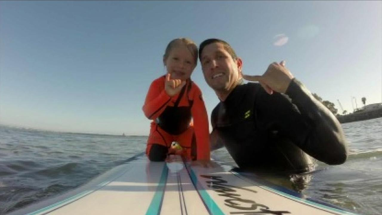 Aviana Zizi, 4, poses with her father, Mark, after a surfing session in an undated photo.