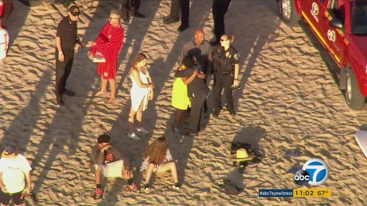 Friends and family of a missing swimmer gathered at Manhattan Beach as crews frantically searched the waters on Tuesday, April 19, 2016.