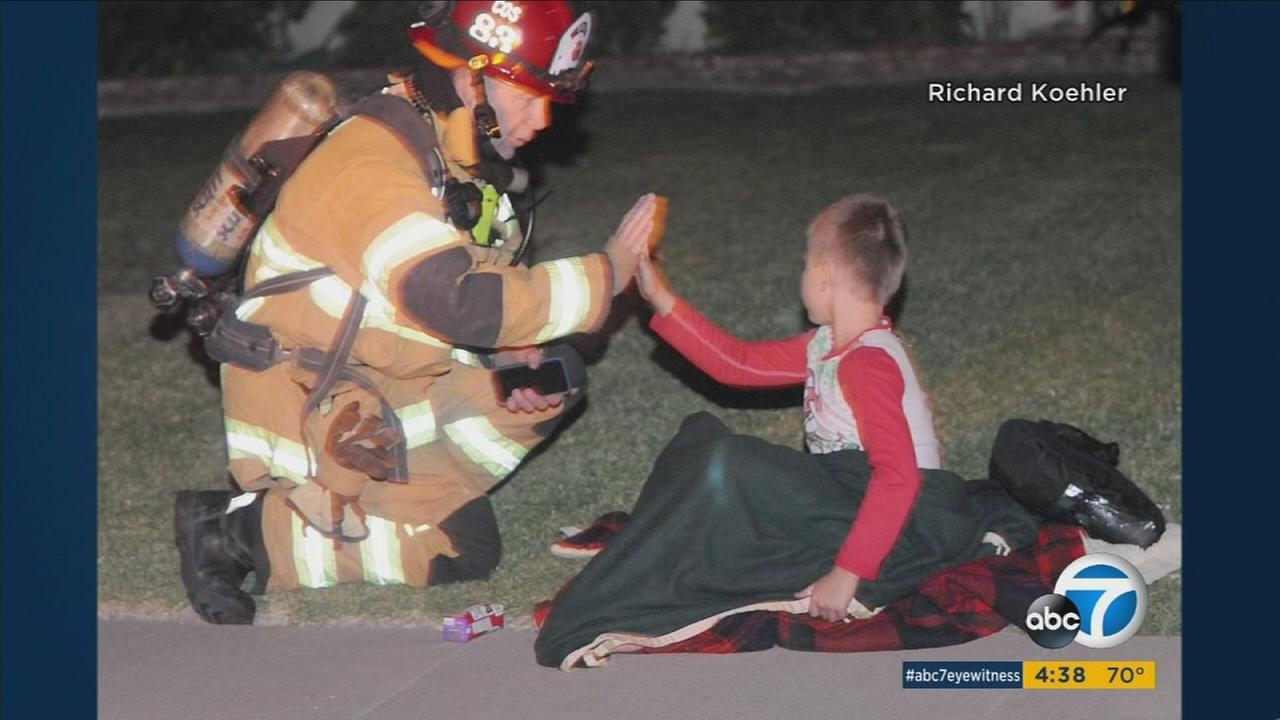 A 7-year-old boy is being credited with saving his father during a fire in Costa Mesa.