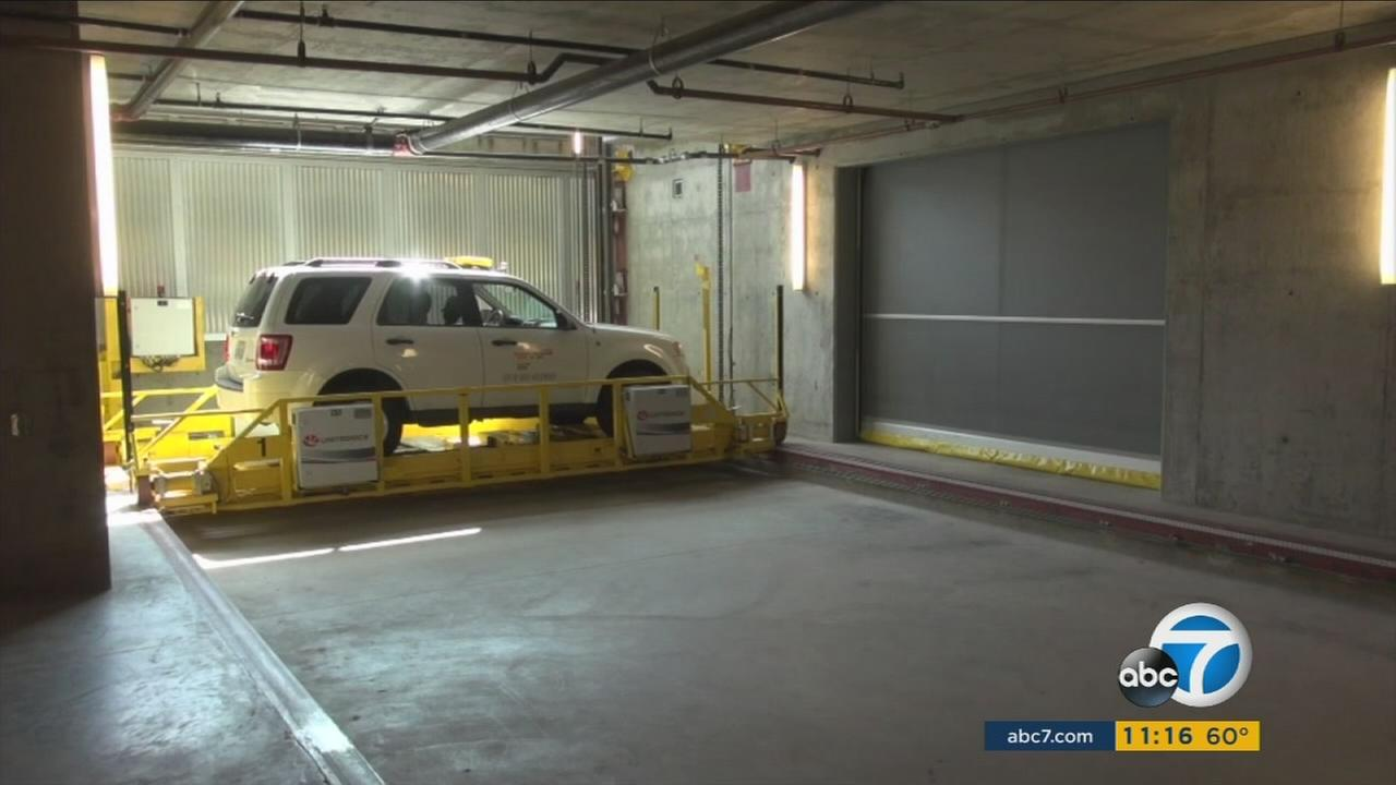 A car is shown being placed into a parking space at the first automatic parking structure in West Hollywood.