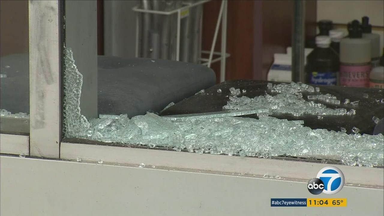 A window is broken on Tuesday, May 31, 2016, after police caught two men breaking into a pharmacy in Beverly Hills, Calif.