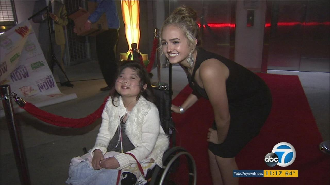 A student in a wheelchair smiles for the camera while on the red carpet heading toward the No Worries Foundation Prom in Hollywood.