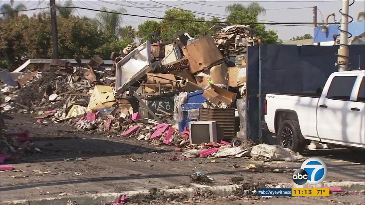 Debris and other pieces of burned commercial buildings involved in a magnesium-fueled fire in Maywood are removed on Thursday, June 16, 2016.