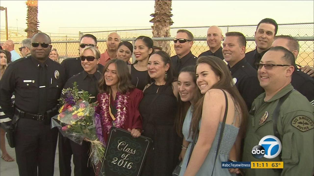 The Cuesta family smiles with their extended family of Los Angeles police officers during a Yorba Linda high school graduation ceremony.