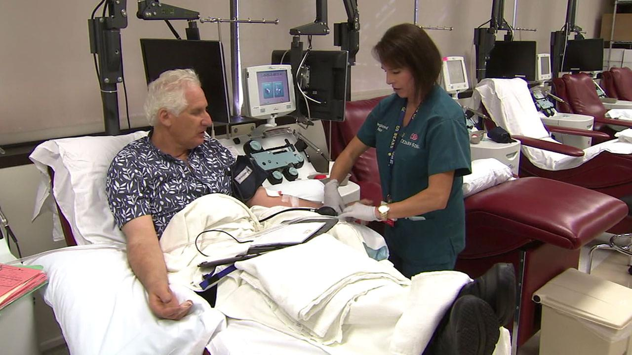 Fred Zaidman sits in a chair as he donates blood to Cedars-Sinai in Los Angeles.