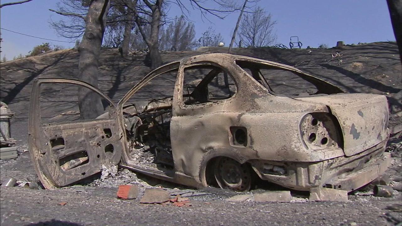 The charred remnants of a car are seen in the Iron Canyon area of Santa Clarita on Monday,  July 25, 2016.
