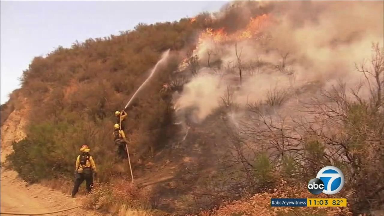 Firefighters work to calm the heavy flames in a portion of the Sand Fire in the Santa Clarita area on Tuesday, July 26, 2016.