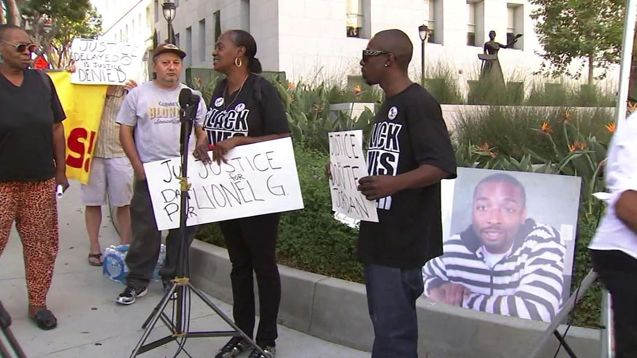 Activists are shown calling for more action to be done in police shooting investigations alongside a photo of Ezell Ford, who was killed by police two years ago.