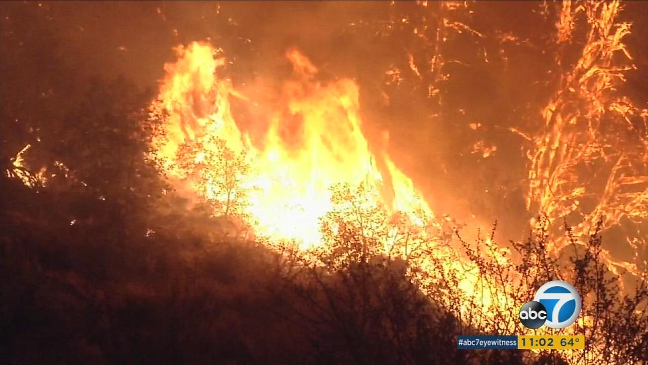 The Blue Cut Fire continued to blaze through Wednesday night, threatening thousands of homes in San Bernardino County.