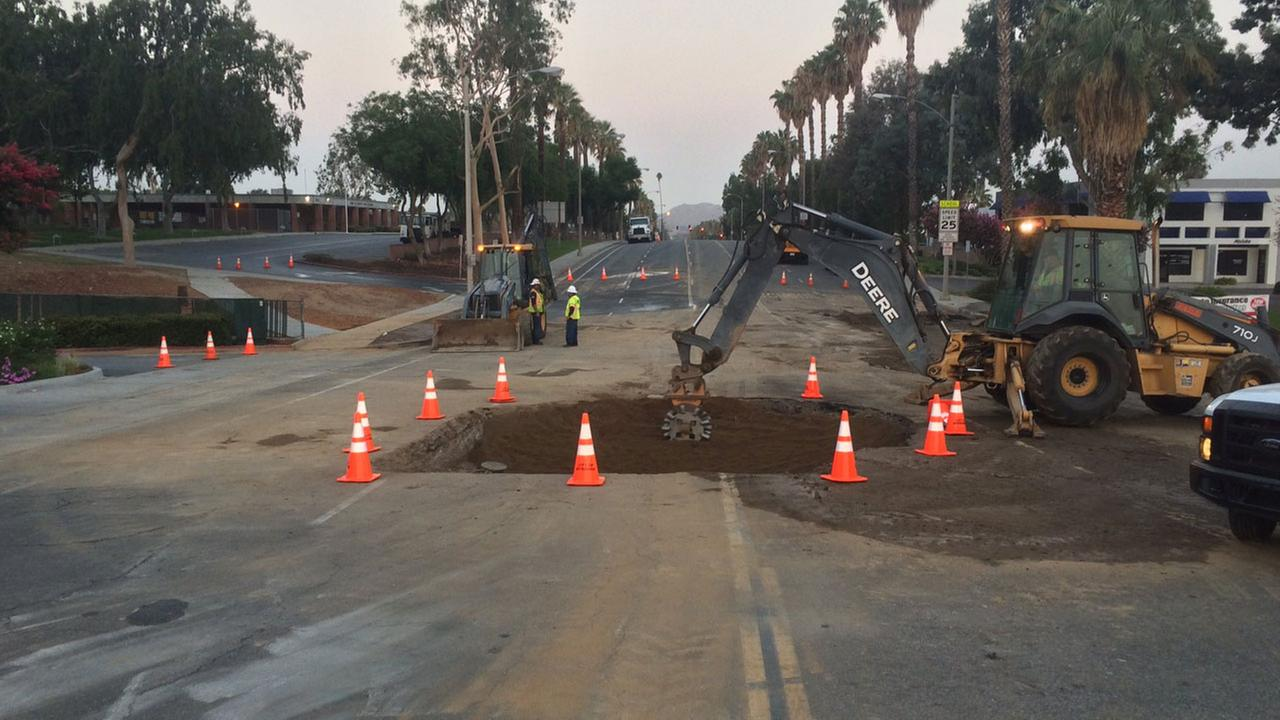 Crews fill a sinkhole caused by a water main leak in Riverside on Thursday, Aug. 25, 2016.