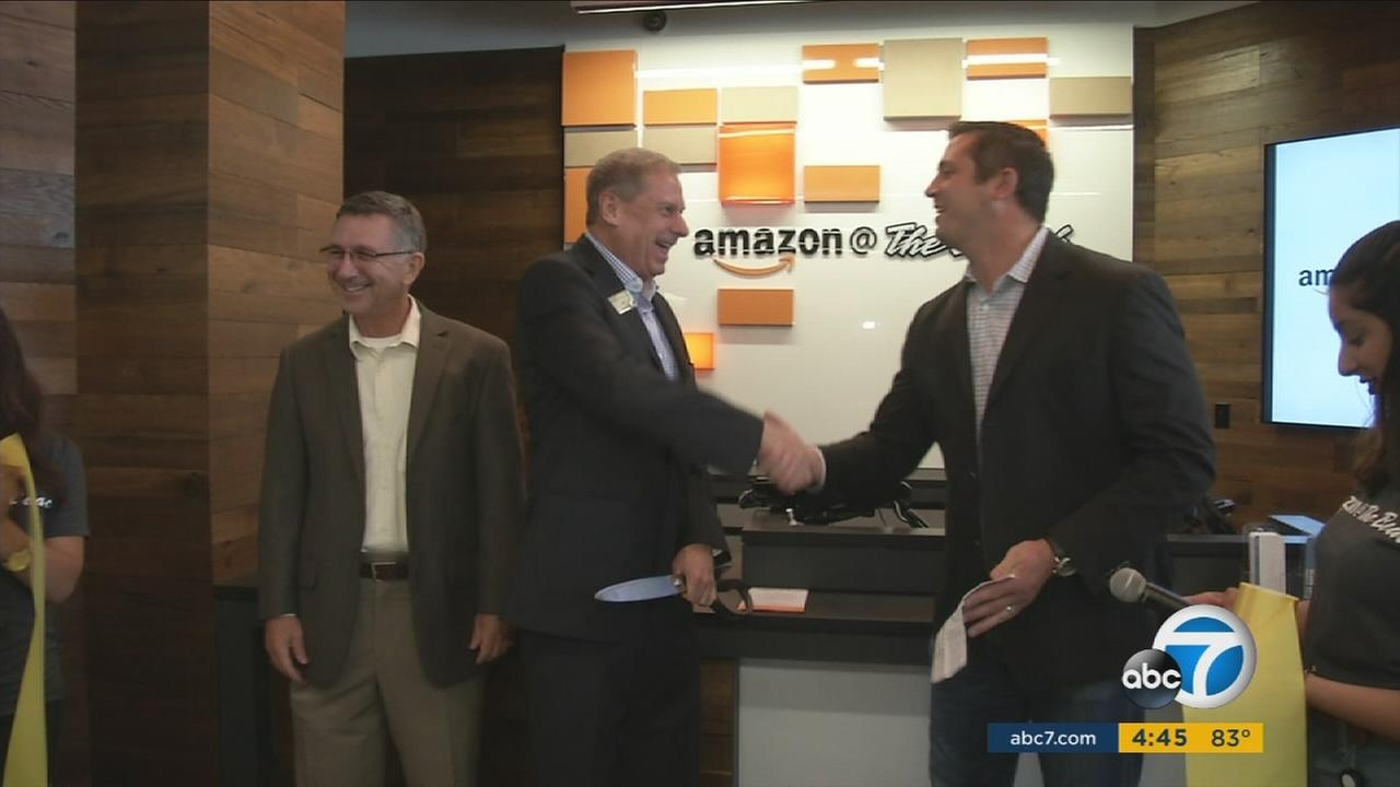 Amazon officials and store managers shake hands during the opening of an Amazon pickup location at California State University Long Beach on Tuesday, Sept. 20, 2016.
