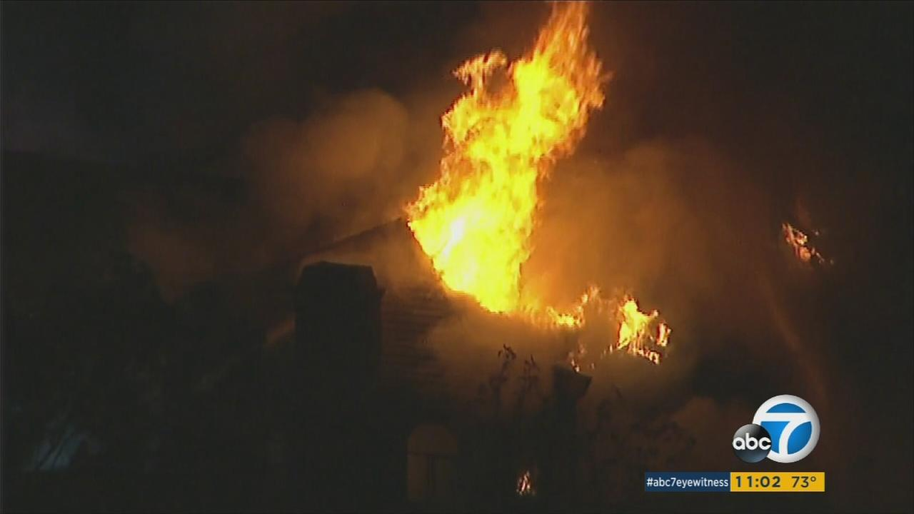 Firefighters battled heavy flames at a hillside Mt. Washington home just north of downtown Los Angeles and at least one civilian was injured, officials said.