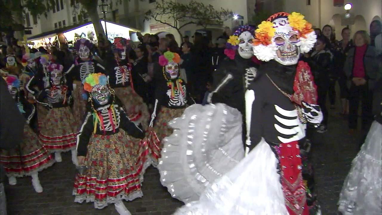 People celebrate Dia de los Muertos along Olvera Street in downtown Los Angeles on Tuesday, Nov. 2, 2016.