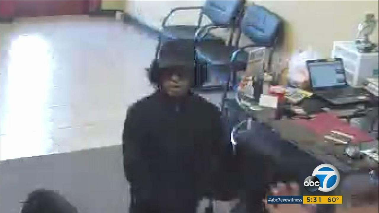 Surveillance video shows a suspect in a wig and sunglasses who robbed a Crown Gold Exchange store in Corona.