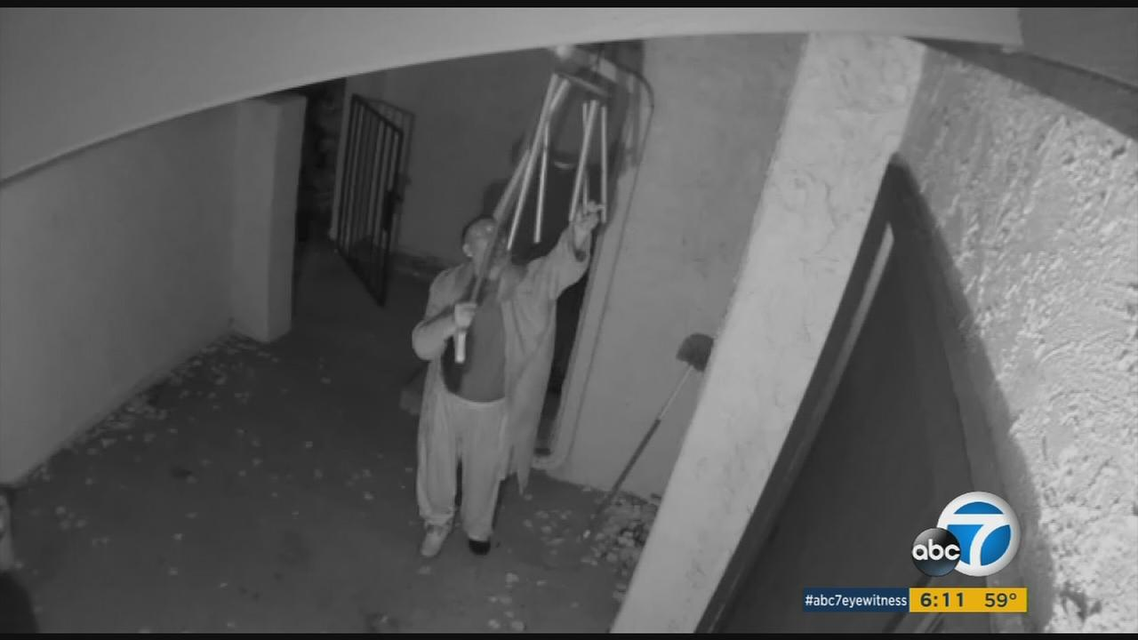 A neighbor, accused of leaving human waste on a womans car in Woodland Hills, is seen harrassing wind chimes.