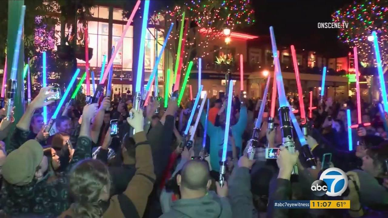 Fans hold a vigil using colorful lightsabers in Downtown Disney as a tribute to late actress Carrie Fisher on Wednesday, Dec. 29, 2016.