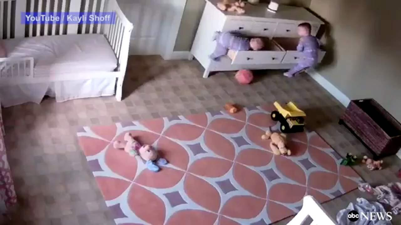 Frightening video shows a dresser falling on two children, trapping one of them while his twin pushes the dresser to free his brother.