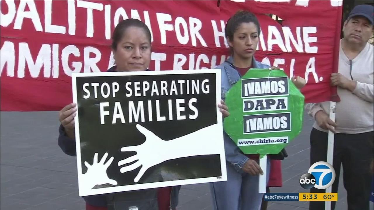 People supporting an Office of Immigrant Affairs hold signs outside during the board of supervisors meeting in downtown L.A. on Tuesday, Jan. 10, 2016.