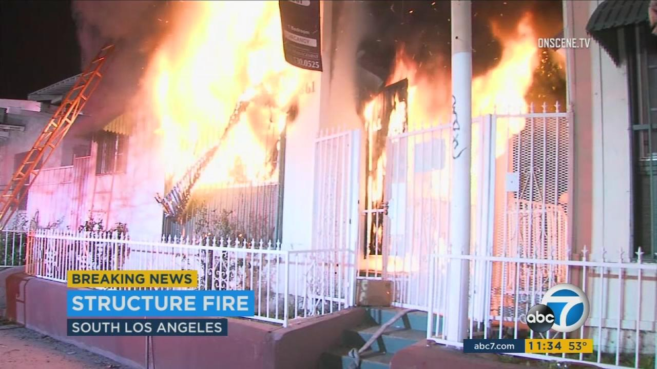 Flames rip through a home in the Vermont Knolls area of Los Angeles, where at least four children were injured Monday, Jan. 17, 2016.