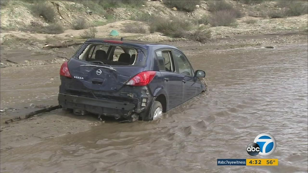 A damaged car sits in the middle of a muddy, flooded creek in Placentia Canyon in the Santa Clarita Valley on Monday, Jan. 23, 2017, after being swept away the night before.