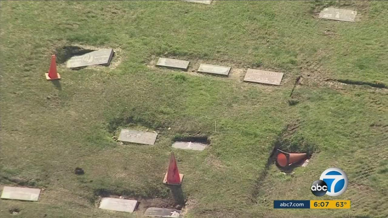 Sunken headstones are shown at a Pomona cemetery after heavy rain storms saturated the ground.