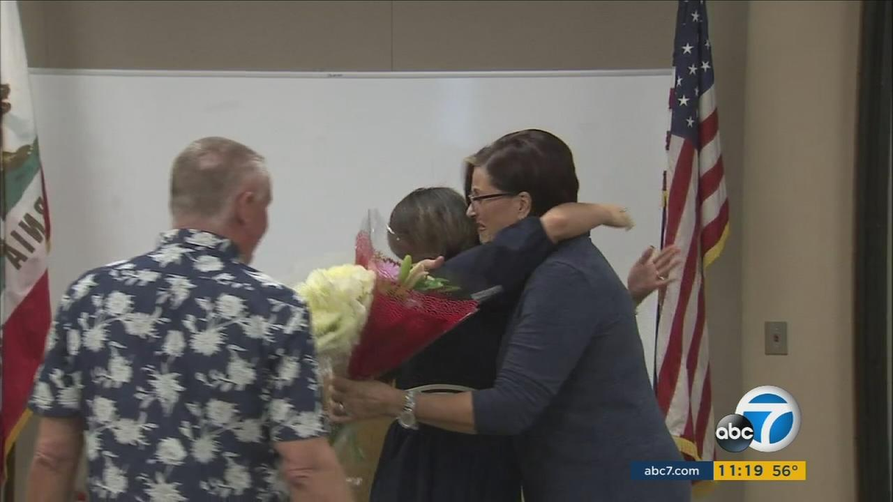 The wife of a man who was saved from cardiac arrest hugs the dispatcher who helped them.