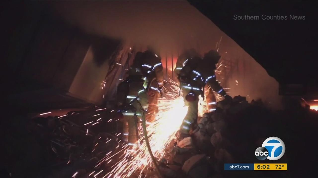 Firefighters use an electrical saw to cut through metal bars as a fire burns near a homeless encampment in Santa Ana on Sunday, Feb. 12, 2017.