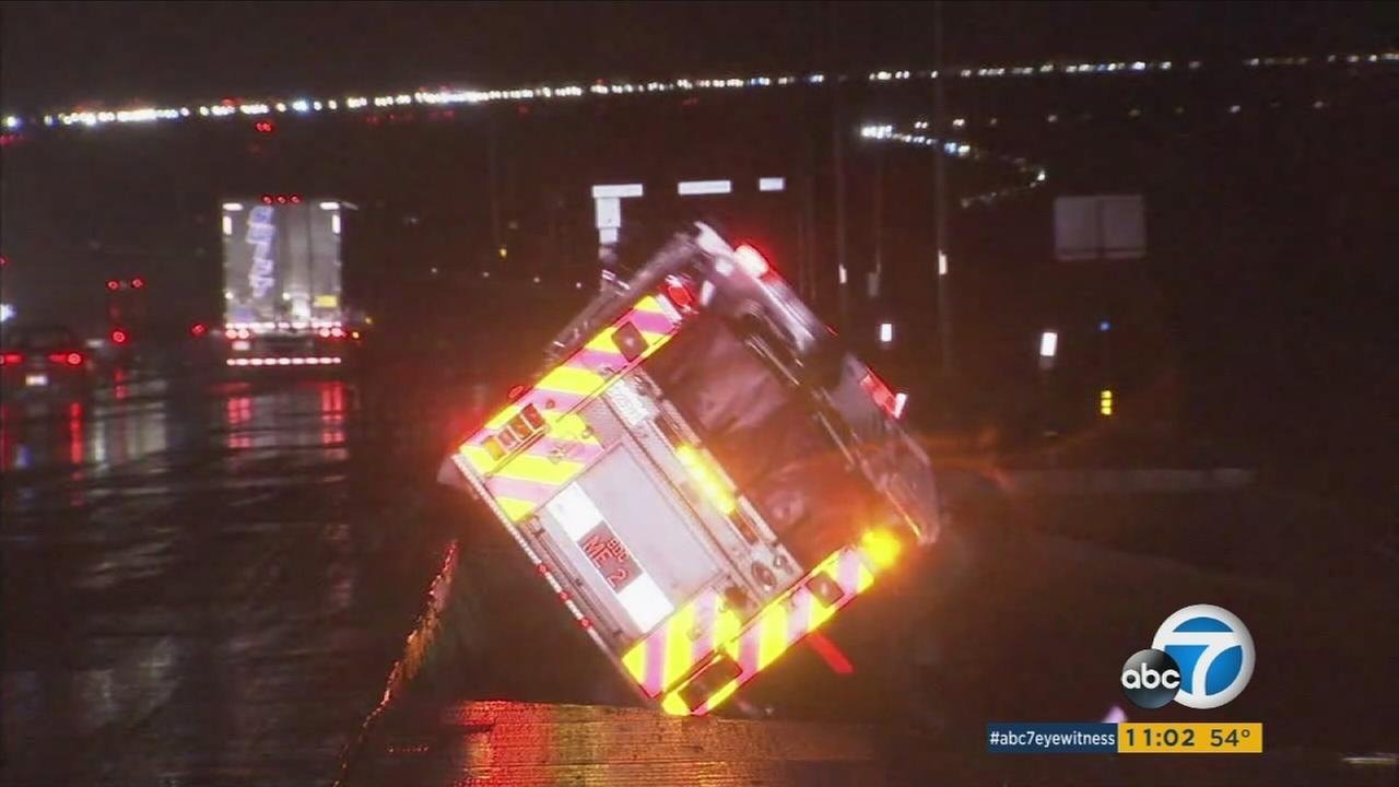 A San Bernardino County fire truck fell over the side of the 15 freeway in the Cajon Pass when the rain-soaked roadway gave out. No firefighters were injured.