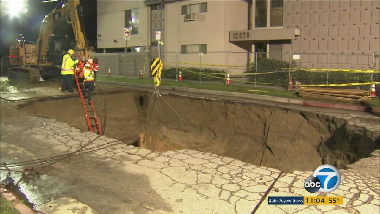 Crews on Saturday were working to repair a massive sinkhole that swallowed two vehicles and briefly trapped one woman inside her car.