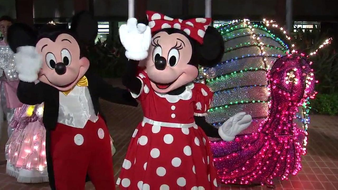 Mickey and Minnie Mouse show off spectacular floats from Disneys Main Street Electrical Parade.