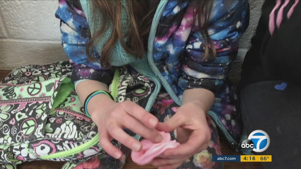 A young girl is seen playing with do-it-yourself slime.