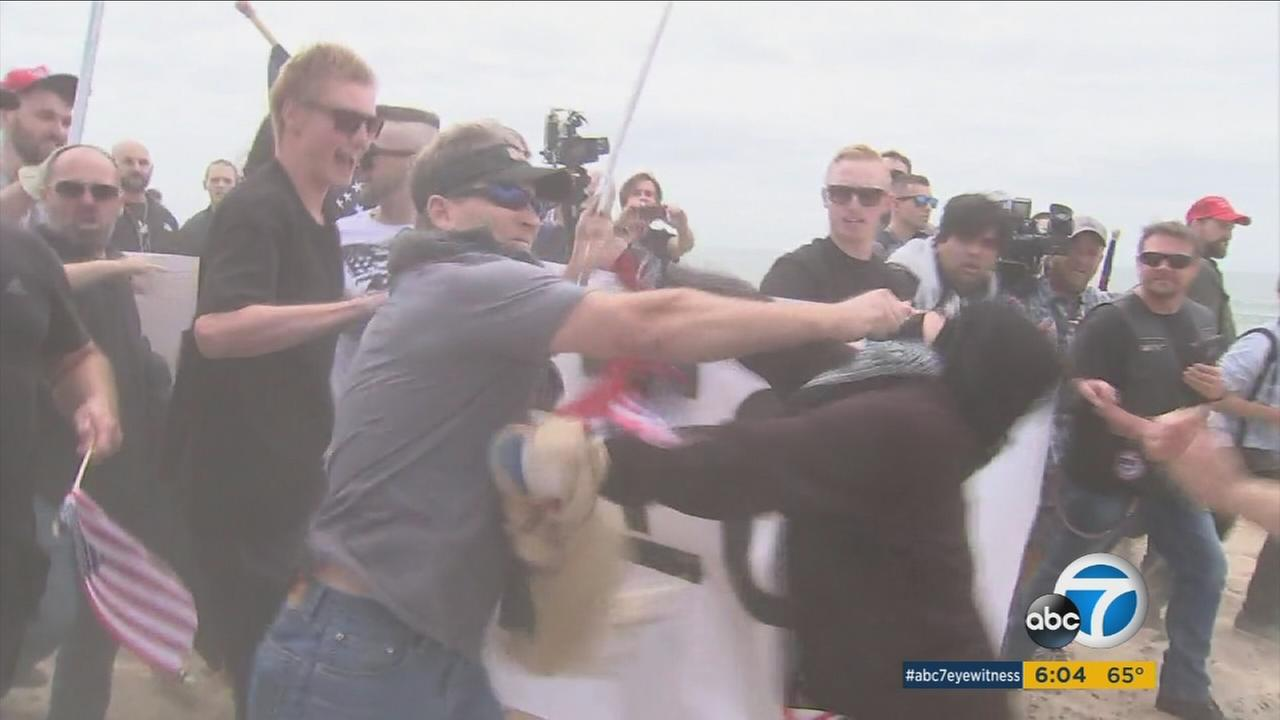A Trump supporter is shown punching a female Trump protester in the face during a Huntington Beach rally and march on Saturday, March 25, 2017.